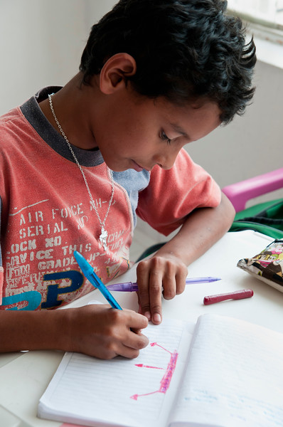Boy draws in his notebook.