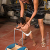 Physical therapist helps child learn to walk using wheeled cart.
