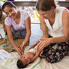 Physical therapist demonstrates therapy to mother.
