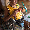 Disabled man is employed assembling balsa wood mobiles.