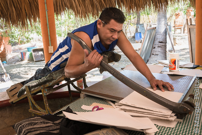 Man using an adapted standing board operates a paper cutter to make notebooks of handmade paper.