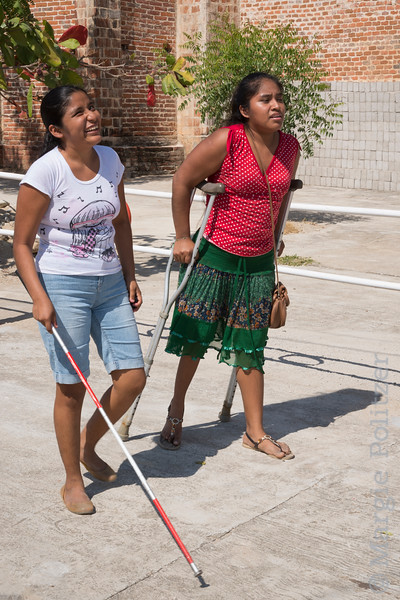 Woman using crutches advises blind woman on walking around village without fear.