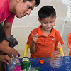 Father encourages son painting a plastic bottle for craft project.