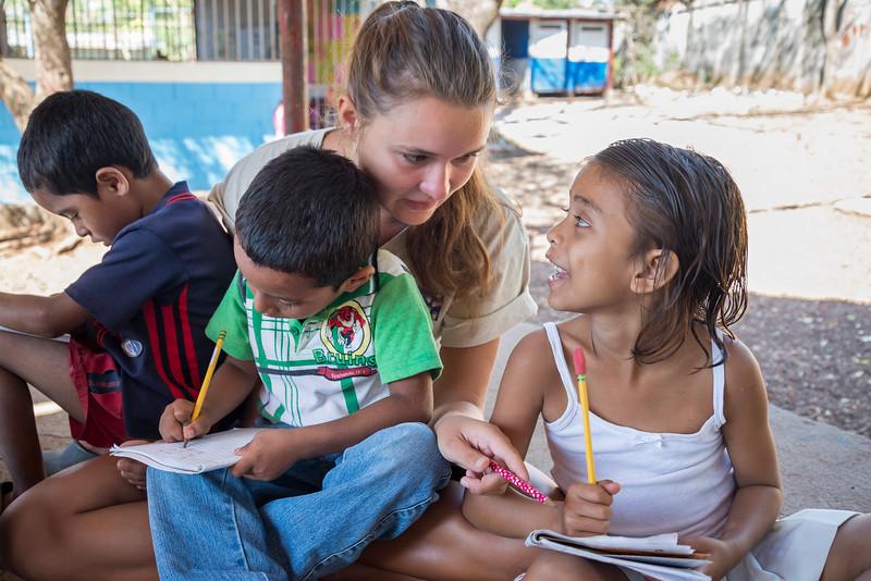 Volunteer helps children learn to write.