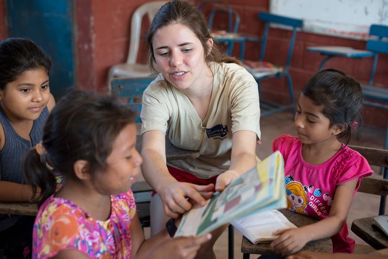 Volunteer helps children learn to read.