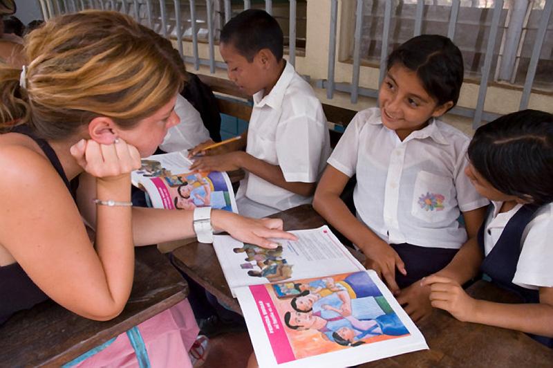 Volunteer helps students learn to read.