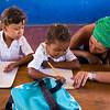 Volunteer helps students learn to write.
