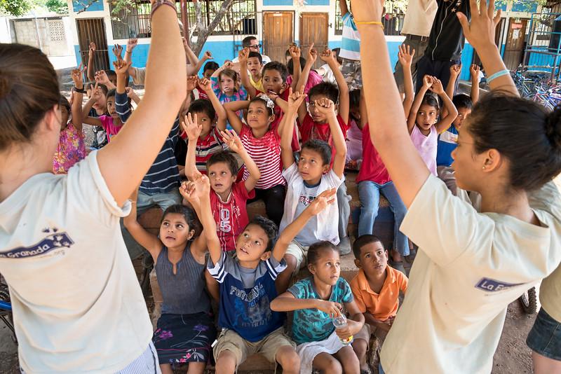 Volunteers lead children in learning game.