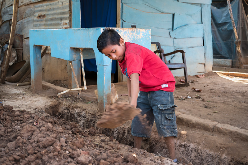 Boy digs ditch to provide running water to his house.