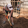 Volunteer digs ditch to provide running water to houses.