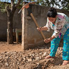 Woman digs ditch to provide running water to houses.
