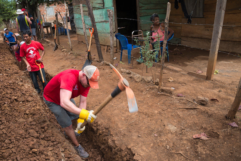 Volunteers and villagers work together digging ditch to provide running water to houses.