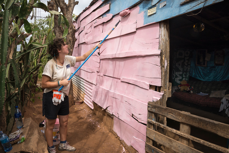 Volunteer paints exterior of house.