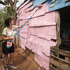 Volunteer paints exterior of house.