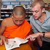 Volunteer helps Buddhist monk with English.
