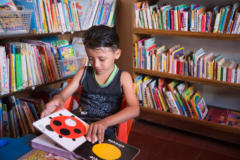 Boy reads book at community library