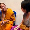 Volunteer speaks English with Buddhist monk.