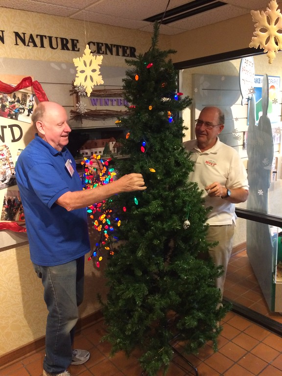 . Chad Felton � The News-Herald <br> REV\'d UP volunteer Jerry Tindall, left, wraps a string of lights on a Christmas tree with Frank Takacs at Penitentiary Glen Nature Center in Kirtland on Nov. 8. Since 2002, REV\'d UP volunteers have donated more than 3,300 hours to Lake Metroparks for their annual holiday exhibit.