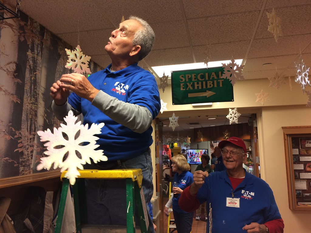 . Chad Felton � The News-Herald <br> REV\'d UP volunteer Tom Miller, left, prepares to hang a snowflake at Penitentiary Glen Nature Center in Kirtland on Nov. 8. Fellow volunteer Gordon Lucas stands at right.