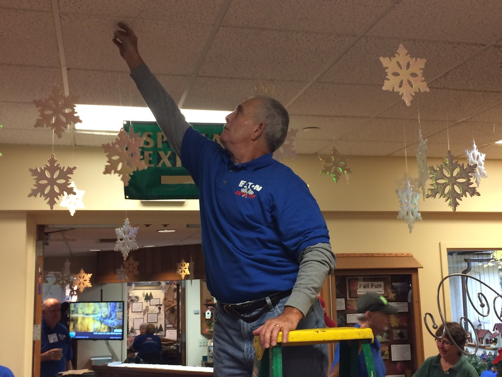 . Chad Felton � The News-Herald <br> REV\'d UP volunteer Tom Miller hangs a snowflake at Penitentiary Glen Nature Center in Kirtland on Nov. 8. For the last 15 years, the group has assisted staff prepare for its annual holiday exhibit.