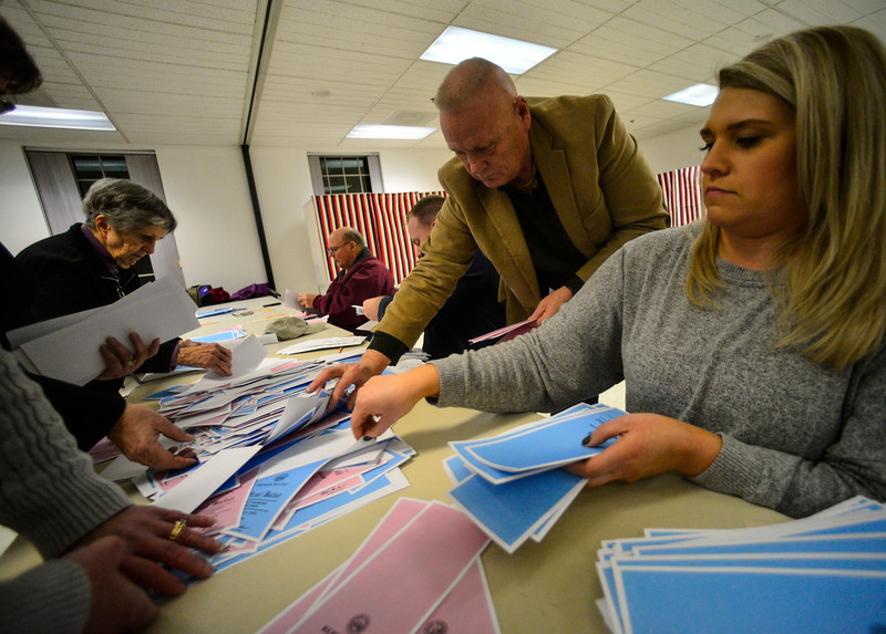 KRISTOPHER RADDER — BRATTLEBORO REFORMER<br /> Michael Carrier, of Hinsdale, N.H., and Megan Kondrat, of Hinsdale, N.H., puts the primary ballots into piles before they start to count the votes at the Millstream Community Center, in Hinsdale, N.H., after the closing of the polls during the New Hampshire presidential primary elections on Tuesday, Feb. 11, 2020.