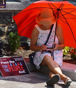 The heat and humidity did not deter this woman from attending a rally in Wilmington, DE. to support voting rights legislation before the Congress in Washington.