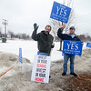 Lunenburg residents Robert Ebersole (left) and Greg Berthiaume wave to passing cars on Massachusetts Ave. with signs in favor of a new middle high school. Voters in the town voted Saturday on the funding mechanism for the school.<br /> SENTINEL & ENTERPRISE / BRETT CRAWFORD