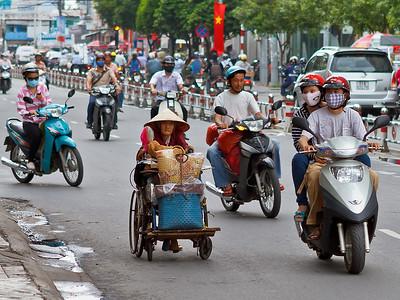 En dan ineens een oud vrouwtje op de weg tussen het drukke verkeer. Ze duwt een rolstoel voort met wat schamele bezittingen, of is het spul om te verkopen? Gelukkig ziet het andere verkeer haar wel, ook al is de dame die achter haar hier de weg opdraait meer bezig met haar mobiele telefoon dan met het verkeer op de weg...
