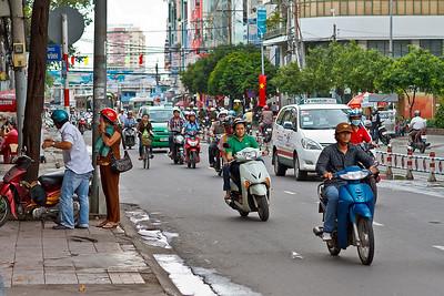 Veel rode vlaggen... En veel motorfietsen!!! Overal de Vinasun taxi's, wij hadden 3 dagen een auto met chauffeur ter beschikking, was prima!  Ik zou hier niet durven rijden want die motorfietsen schieten links en rechts voorbij. Als het stoplicht rood is dan nemen ze het voetpad, dus ook als voetganger moet je constant goed opletten!!  Zebrapaden hebben ze ook, maar dat wil hier niks zeggen. Goed blijven kijken, want alles wat kan rijden rijdt gewoon door als je wil oversteken!!!
