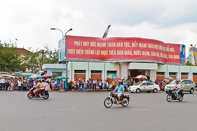 Busstation in Ho Chi Minh City met motorfietsen op de voorgrond. De motorfietsen worden gebruikt voor het vervoer van hele families, hier een met 3 volwassenen!