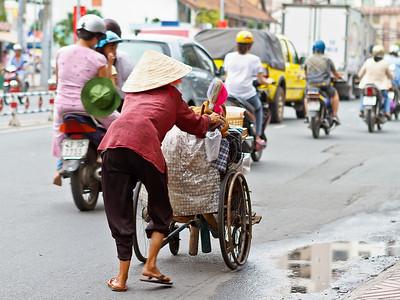En zo sjokt ze hier door Ho Chi Minh, wie weet waar ze nog helemaal naartoe moet... Links een man, vrouw en kind samen op de motorfiets.