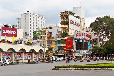 Links een hoek van de Ben Thanh markt. Midden op de foto een riksja bij de markt. Verder opvallend de daktuinen achter het Sharp reclamebord.