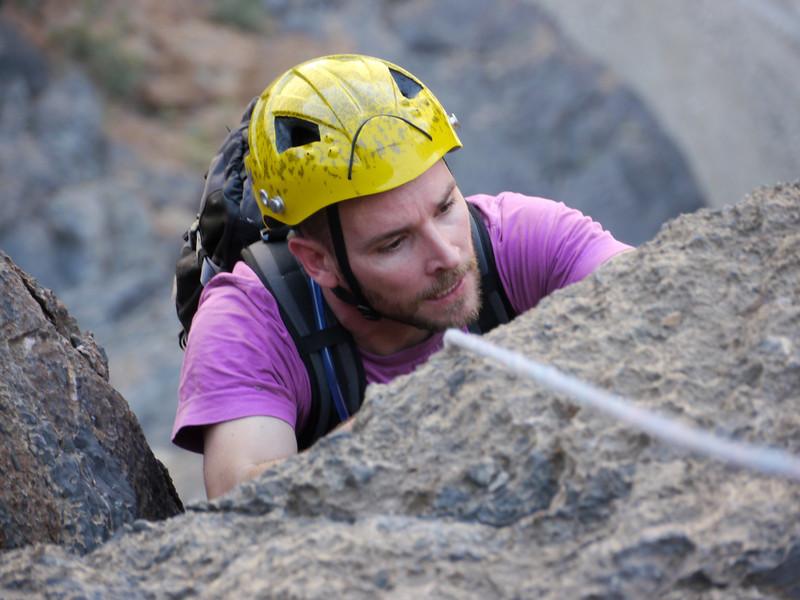 Seb scrute le rocher pour trouver les meilleures prises à la sortie de la deuxième longueur difficile...