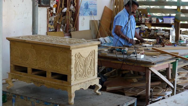 Dans un atelier, un menuisier propose des meubles sur mesure...