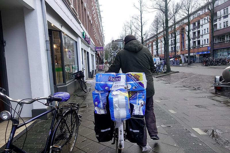 Nederland, Amsterdam, man met volle fietstassen in de eerste van Swindenstraat, 18 januari 2018, foto: Katrien Mulder