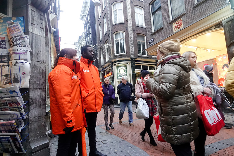 Nederland, Amsterdam, Warmoesstraat, host en hostess van de Gemeente, zijn aanspreekpunt voor bezoekers van toeristische locaties in Amsterdam, host and hostess of the Municipality, can be contacted by visitors of tourist locations in Amsterdam20 januari 2018, foto: Katrien Mulder