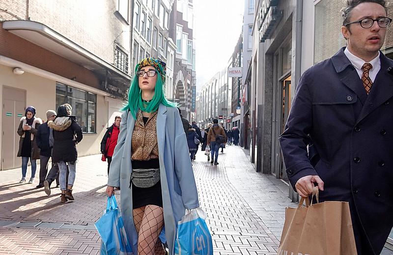 Nederland, Amsterdam, 26-03-18, modieus geklede jonge vrouw loopt met Abert Heijntassen over de Nieuwendijk. Haar haren zijn groen en hebben dezelfde kleur als haar jas. Ze draagt netkousen; foto: Katrien Mulder/Hollandse Hoogte