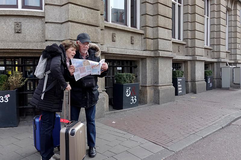 Nederland, Amsterdam, Nieuwezijds Voorburgwal, Twee toeristen van middelbare leeftijd met rolkoffers zoeken de weg met behulp van een plattegrond, 26-03-18, foto: Katrien Mulder/Hollandse Hoogte