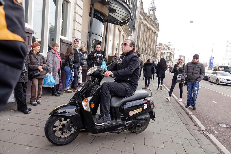 Nederland, Amsterdam, 26-03-18, Een man zit op zijn scooter die midden op  het trottoir staat. foto: Katrien Mulder/Hollandse Hoogte