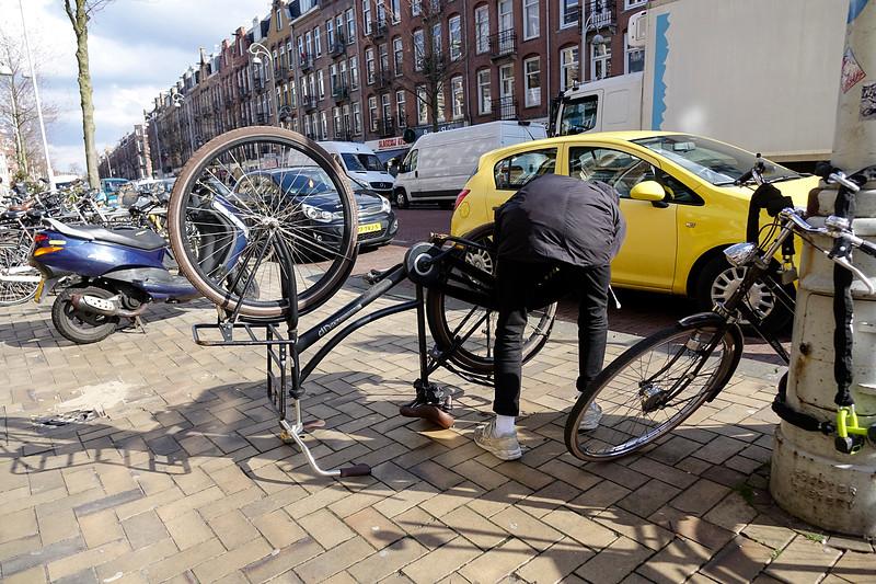 Nederland, Amsterdam; 29-03-2018, In de Javastraat in de Indische Buurt, plakt een man de achterbamd van zijn fiets, foto: Katrien Mulder/Hollandse Hoogte