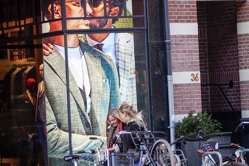 Nederland, Amsterdam; 29-03-2018, Twee vrouwen lopen in de Willemsparkweg langs de  monumentale homo-erotische reclame aan de pui van de zaak Suit Supplies, foto: Katrien Mulder/Hollandse Hoogte