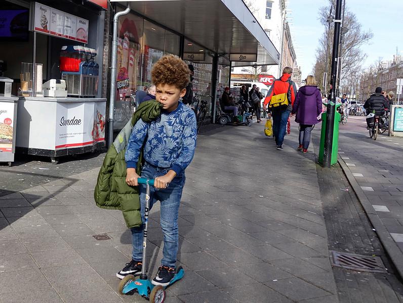 Nederland, Amsterdam, 04-06-2018,  jongen rijdt met zijn step op de stoep Hij heeft zijn jas uitgetrokken vanwege het mooie weer en houdt die vast met zijn mond,  foto: Katrien Mulder