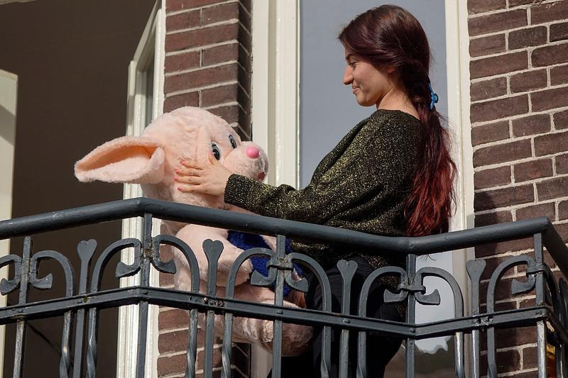 Nederland, Amsterdam, 04-06-2018, Jonge vrouw staat op het balkon met een enorm groot knuffelbeest dat ze zojuit heeft uitgeklopt, foto: Katrien Mulder/Hollandse Hoogte