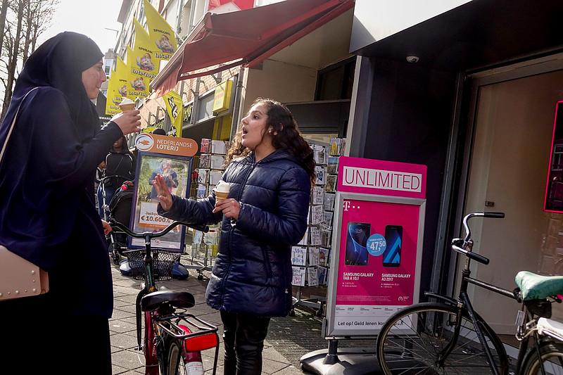 Nederland, Amsterdam, 04-06-2018,  In de van der Swindenstraat eten een vrouw, gekleed in Khimar en een meisje een ijsje terwijl ze in een druk gesprek verwikkeld zijn, foto: Katrien Mulder/Hollandse Hoogte