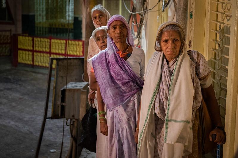 Some of the widows of Vrindavan taking shelter from the rain. Near the Shri Bhagwan Bhajan Ashram.