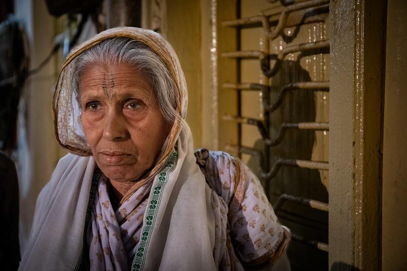One of the widows of Vrindavan taking shelter from the rain. Near the Shri Bhagwan Bhajan Ashram.