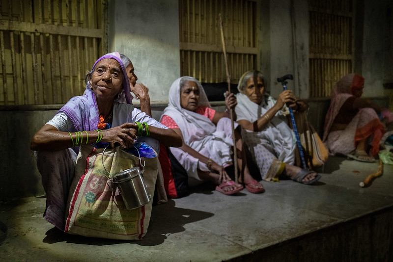 Some of the widows of Vrindavan taking shelter from the rain. Just outside the Shri Bhagwan Bhajan Ashram.