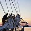 The crew pulls together to furl a sail at sunset.
