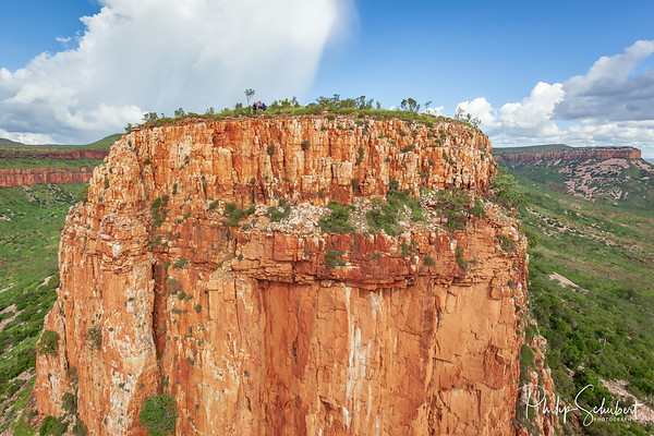 Aerial view of man holding Australian Flag on top of the iconic cliffs and high plateau of the Cockburn Range, El Questro Station, Kimberley, Australia.