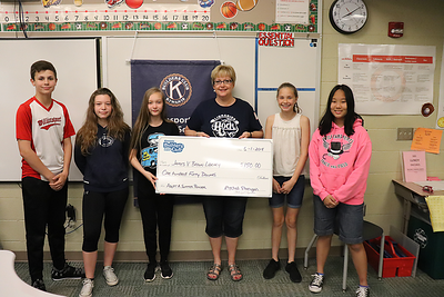 James V. Brown Library's Chief Financial Officer Kristin Caringi, center,  accepts a $150 donation to the Adopt-a-Summer-Reader Program.  From left are Builders Club members Caleb Fausnaught, Savannah Grove, Mychal Flanigan, Sarah Spring and Marcella Fisher.
